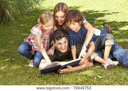 Happy family with children reading a book together in a garden