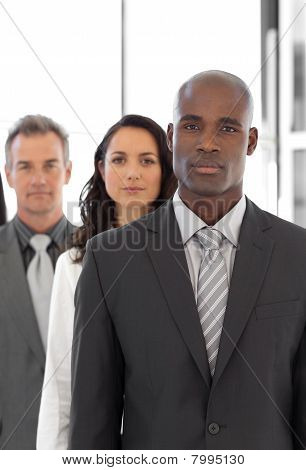 Serious Ethnic Business Leader In Front Of Team