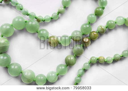 String of nephrite beads closeup as a background poster