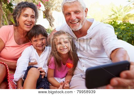 Grandparents With Grandchildren In Garden Taking Selfie