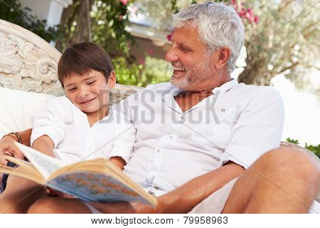 Grandfather And Grandson Sitting In Garden Reading Book