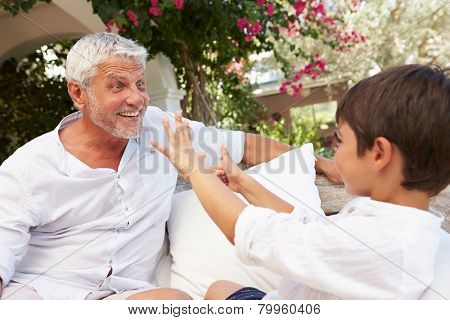 Grandfather At Home Sitting On Outdoor Seat With Grandson