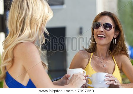 Two beautiful young woman outside at a city cafe laughing and drinking coffee poster