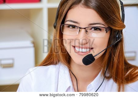Friendly smiling young woman surrort phone operator at her workplace in the office. Headset. Customer service.