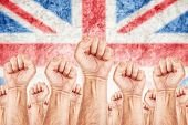Great Britain Labor movement workers union strike concept with male fists raised in the air fighting for their rights British national flag in out of focus background. poster