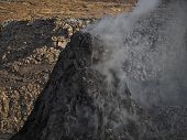 Smoking pinnacle in the Erta Ale volcano area. The lava flow formed incredible waves and patterns after each eruption. Located in Ethiopia, close to the border with Erithrea. poster