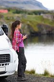 Travel woman by mobile motor home RV campervan. Traveler relaxing camping and enjoying traveling on Iceland in recreational vehicle. Girl enjoying coffee in Icelandic nature landscape. poster