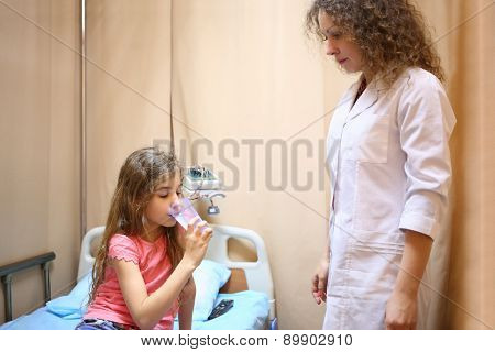Girl sitting on a bed and drinking water near medical worker in a hospital ward