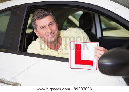 Man holding a learner driver sign sitting behind the wheel at new car showroom