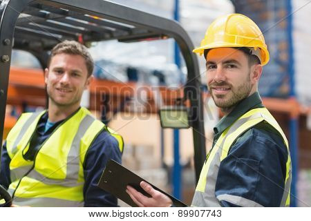 Smiling warehouse worker and forklift driver in warehouse