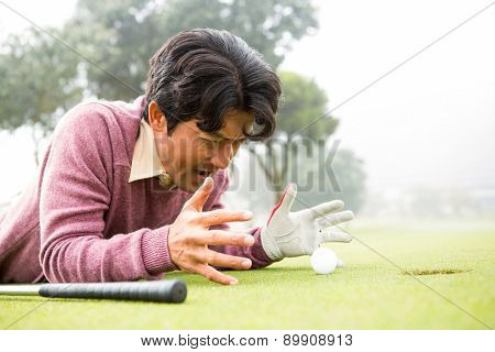 Golfer lying near golf ball at golf course