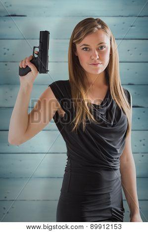 Femme fatale pointing gun up against wooden planks