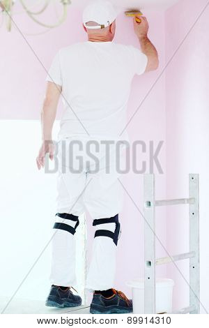 Finisher with brush in hand standing on scaffolding and painting walls near ceiling