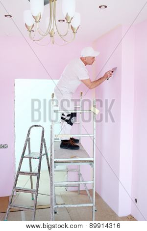 Man with trowel in hand standing on scaffolding in pink room