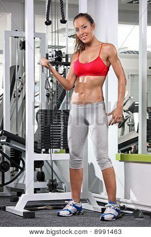 Žena pracující Out na Fitness zařízení v tělocvičně