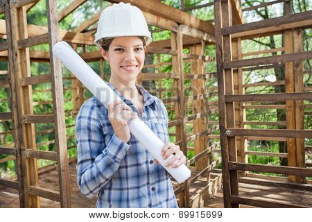 Portrait of smiling female engineer holding blueprint in wooden cabin at construction site