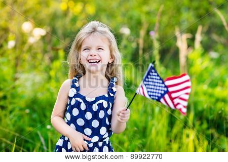 Pretty Little Girl With Long Curly Blond Hair Holding An American Flag, Waving It And Laughing On Su