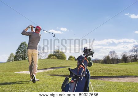 Male golf player swinging golf club, with golf bag and beautiful fairway in background.