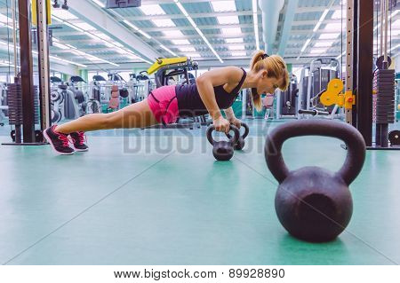 Woman doing pushups over kettlebells in crossfit training