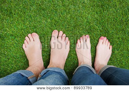 Couple legs standing together on grass