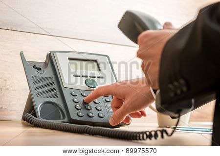 Closeup of businessman hand holding a landline telephone receiver dialing a phone number in order to make a call. poster