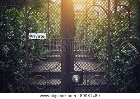 Vintage metal gate with garden view in background.