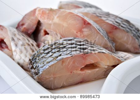 Portion Cut Of Fresh Tilapia Fish On Plate