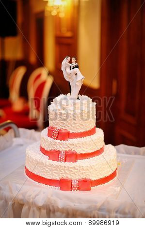 Three-tiered White Wedding Cake With Red Ribbons