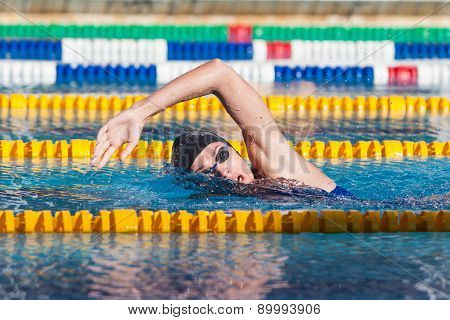 Man swims crawl in the pool, goggles, hat. poster