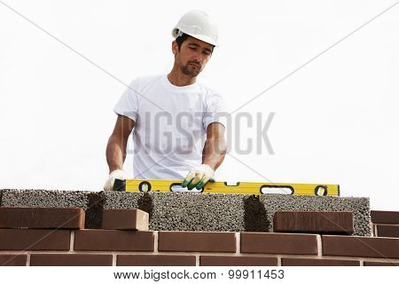 A mason using a level to check his wall
