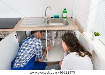 Plumber Showing Damage In Sink Pipe To Woman