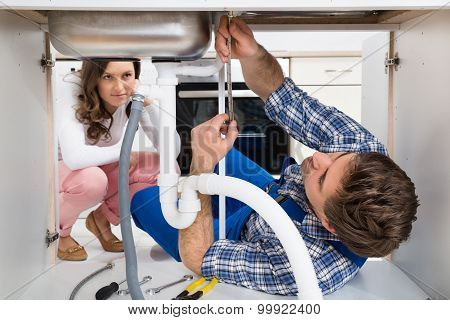 Worker Fixing Sink In Front Of Woman In Kitchen