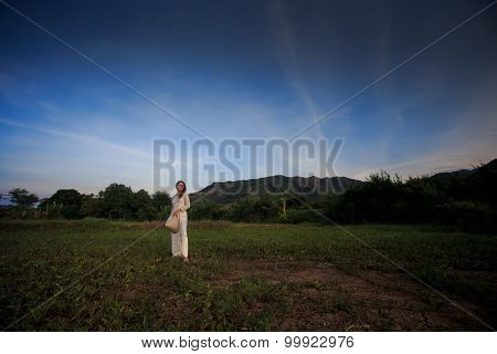Blonde Girl In Vietnamese Dress With Hat In Hand On Field