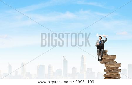 Young businessman with suitcase sitting on pile of old books and showing direction