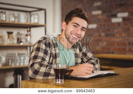 Portrait of smiling hipster having coffee and writing in planner at coffee shop