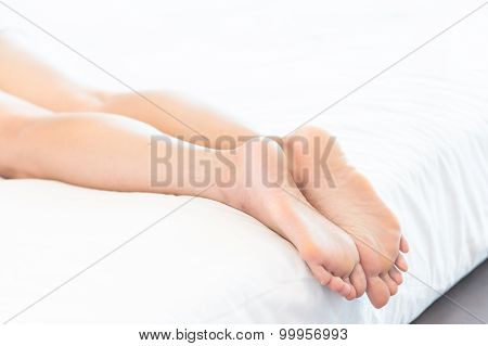 Young Woman Lying In Bed With Closeup Of Bare Feet