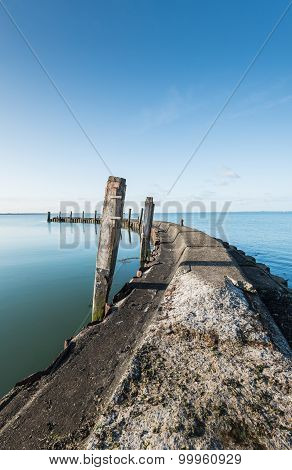 Old Jetty With Wooden Bollards On A Windless Day