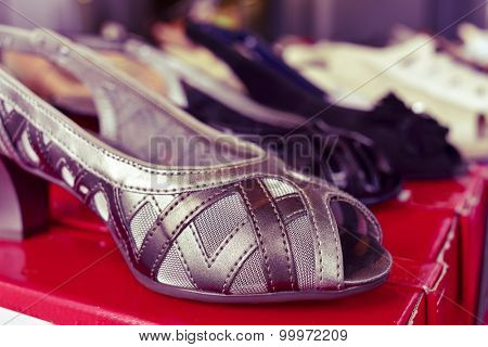 closeup of some different woman shoes on sale in a street market, with a filter effect