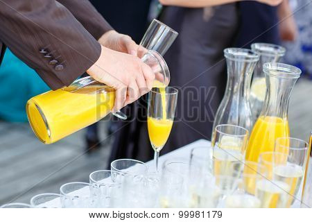Hand Of A Man Pouring Orange Juice On A Wedding
