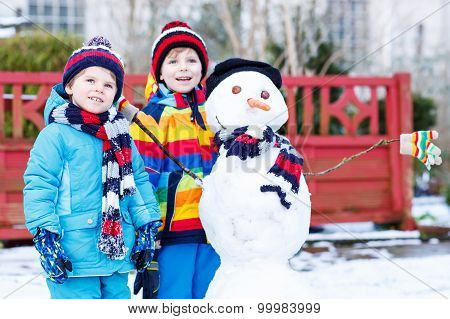 Two Little Friends Making A Snowman, Playing And Having Fun With Snow