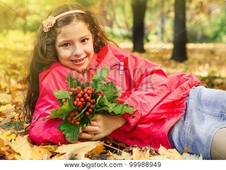 Smiling little  girl holding bouquet of ripe ashberries, sitting in a yellow sunny park