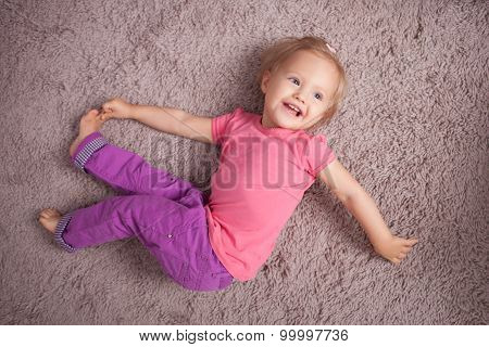 Cute small baby is relaxing on flooring
