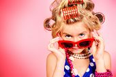 Fashionable little girl in her mother's hair curlers and pin-up sunglasses. Kid's fashion, cosmetics. Pin-up style. poster