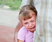defenseless little girl crying under the protection of the parent poster