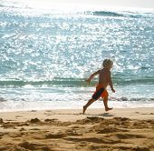 Boy running along seashore sparkling sunlight poster