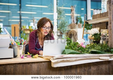 Mid adult female florist using laptop at counter in flower shop