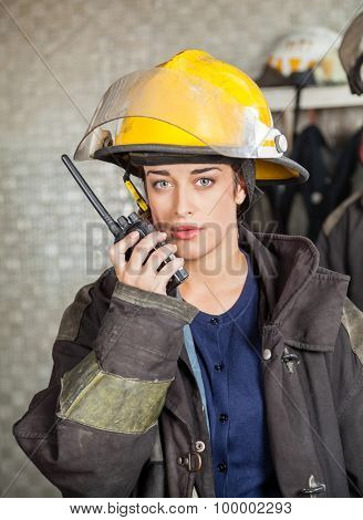 Portrait of confident firewoman using walkie talkie at fire station