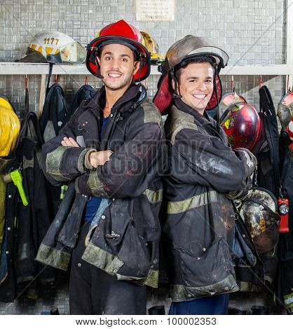 Portrait of happy firefighters standing arms crossed at fire station