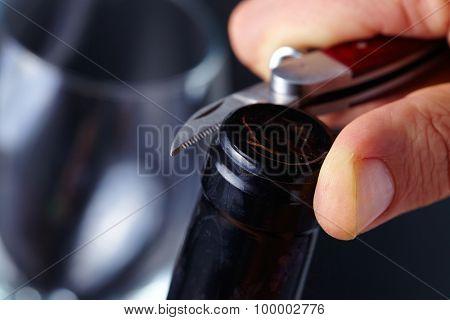 man opening a bottle of wine