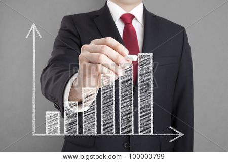 Businessman drawing a growing chart with chalk.